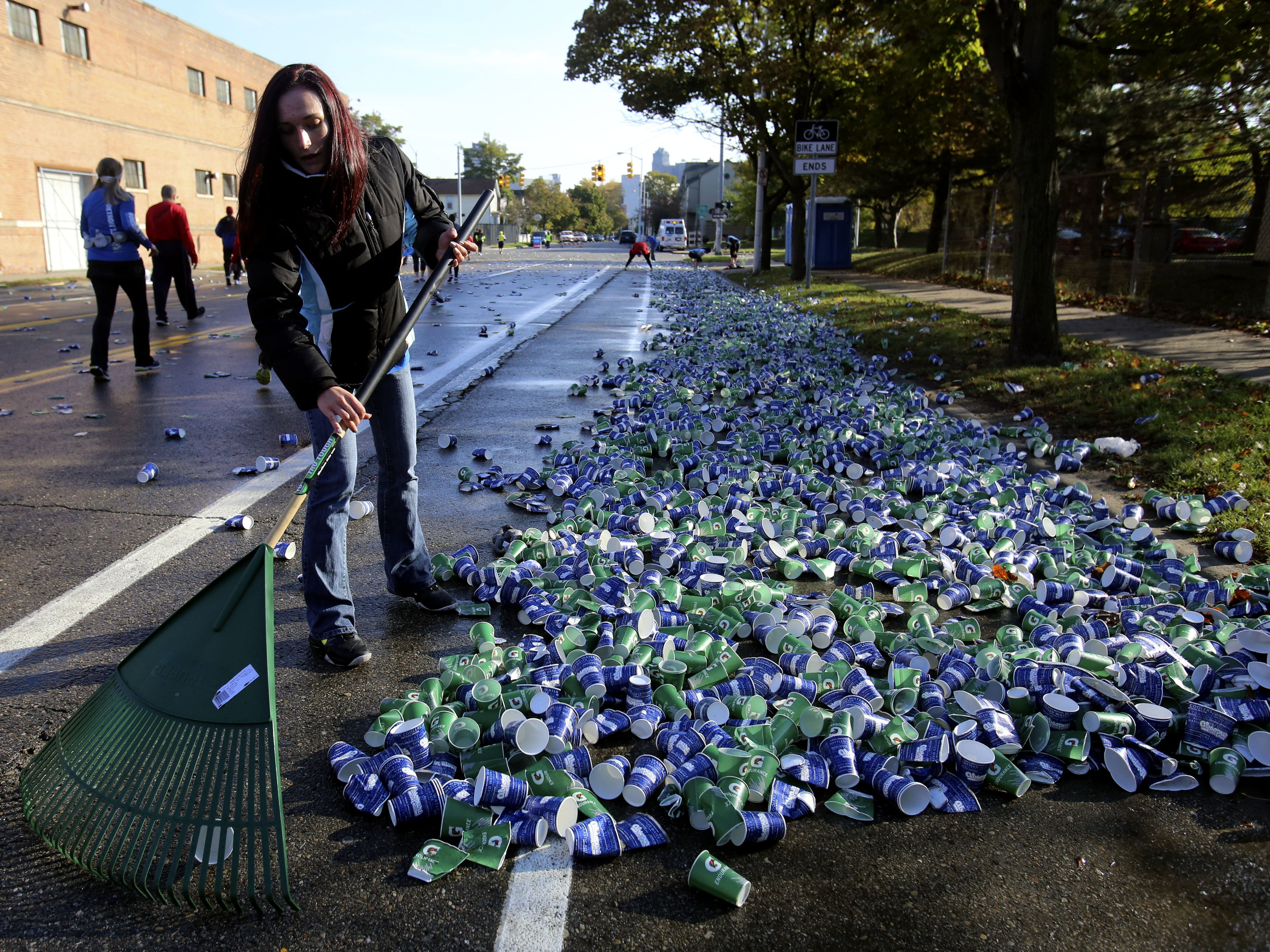 Andrea Mitrache, 19, of Sterling Heights cleans up discarded water cups during the 36th Annual Detroit Free Press/Talmer Bank Marathon in Detroit on Sunday, Oct. 20, 2013.