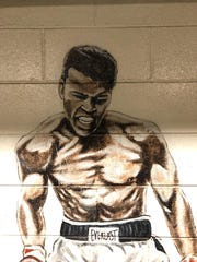 Artist Tony RoKo's first mural as part of the Wayne Assembly Plant beautification program to boost company morale. It features Muhammed Ali knocking out Sonny Liston. Painted in 1991.
