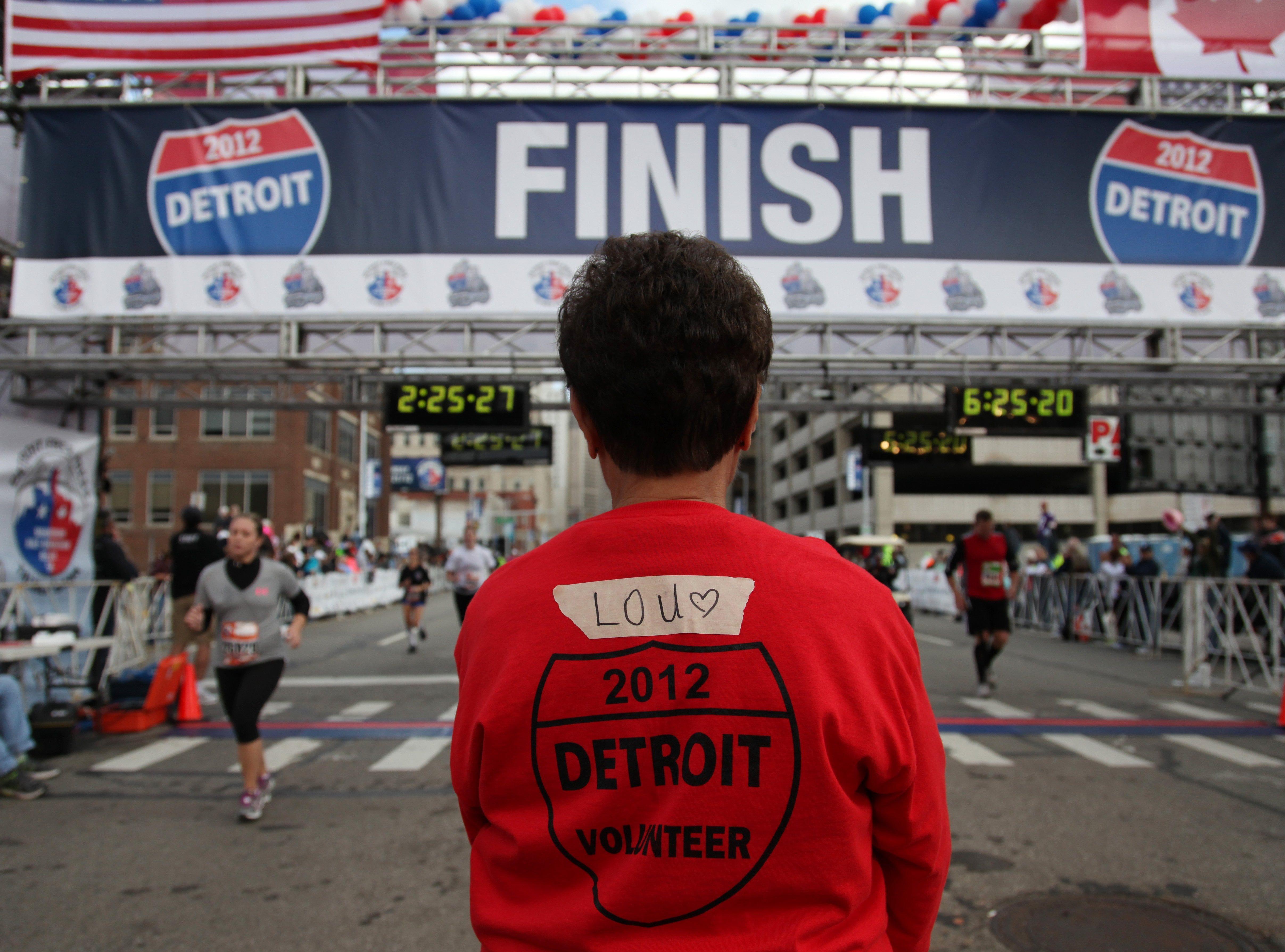 Race volunteer Lou Marossy works the finish line at the Detroit Free Press/Talmer Bank Marathon in Detroit, Sunday, Oct. 21, 2012.
