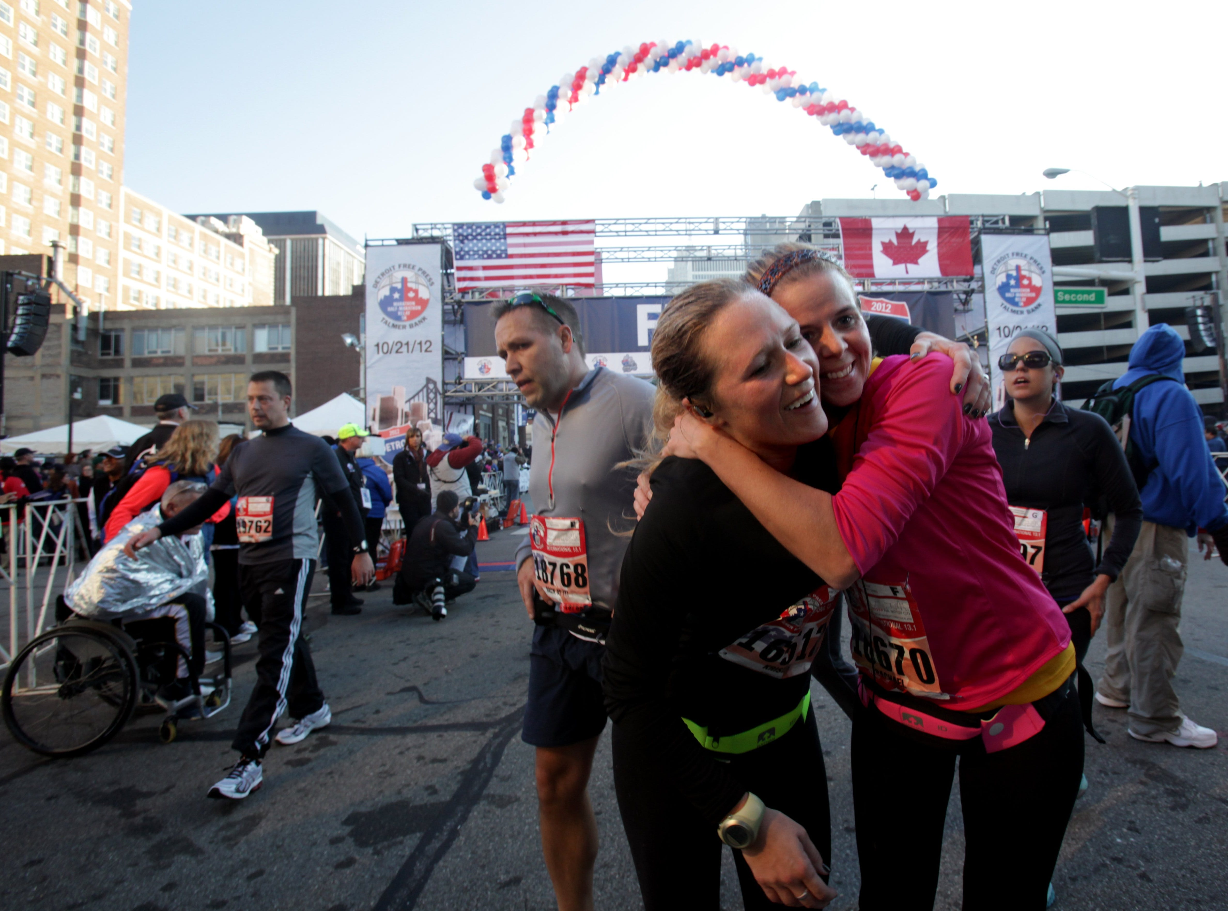 From left, Kristin Thomas, 32, of Lambertville and Rachel Debarr, 31, of Toledo, Ohio, embrace at the finish line at the Detroit Free Press/Talmer Bank Marathon in Detroit,  Mich., Sunday, Oct. 21, 2012.