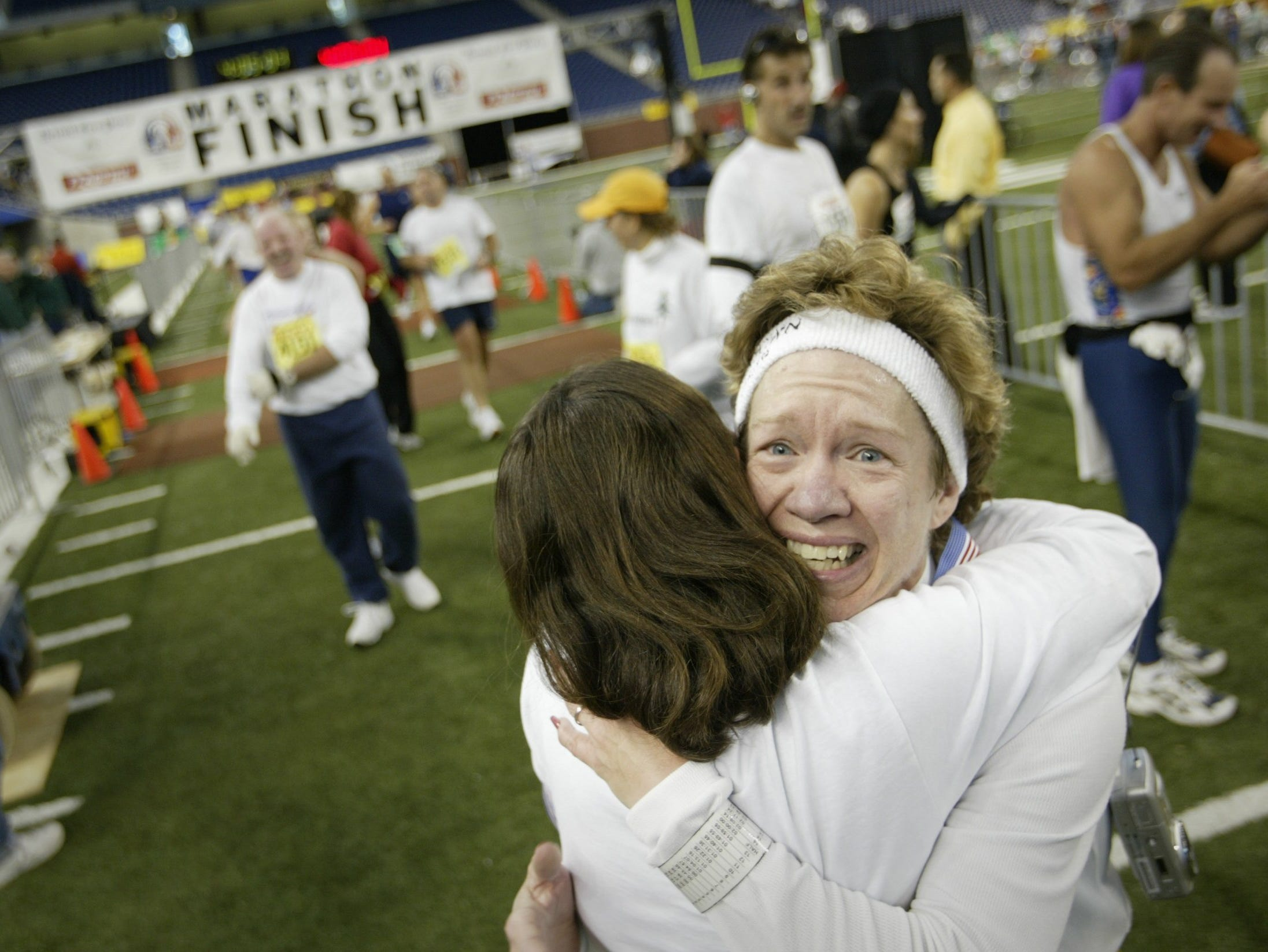 Colleen Sholtis of Rockford, MI, reacts after getting a medal and hug from volunteer Lindsay Parsell of Troy upon finishing the 26th Annual Detroit Free Press / Flagstar Bank Marathon on Sunday October 5, 2003.