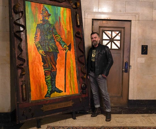 "Artist Tony Roko poses next to his painting titled ""The Commissioner"" on display at the Detroit Foundation Hotel in downtown Detroit on Friday, October 12, 2018."