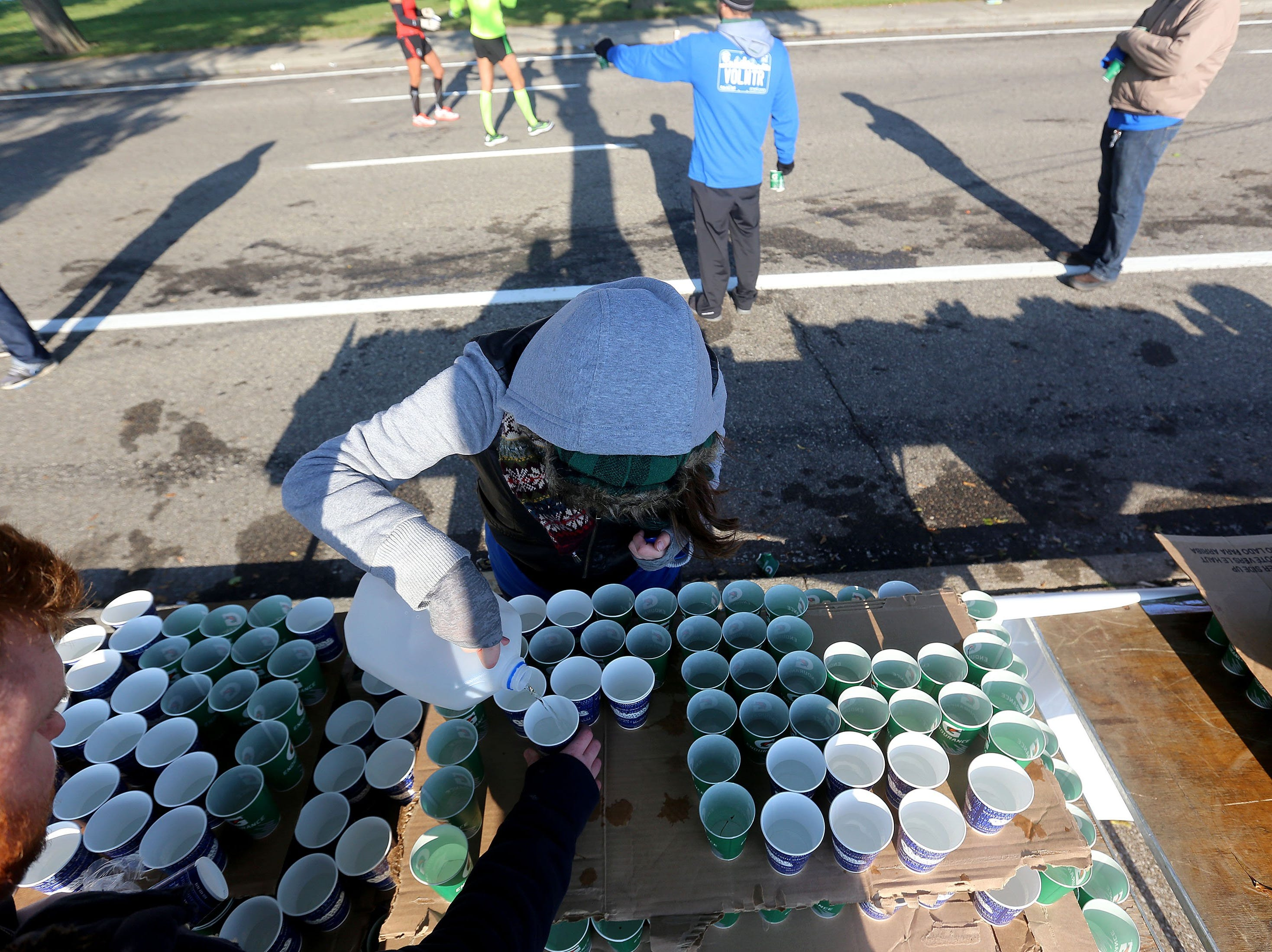 Volunteers hand out water to thirsty runners on Belle Isle during the 36th Annual Detroit Free Press/Talmer Bank Marathon in Detroit on Sunday, Oct. 20, 2013.