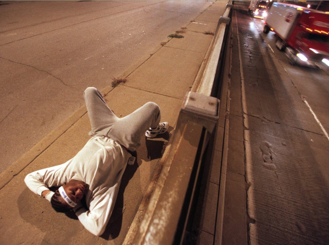 Mike Garacious, of Flint, attempts to get a brief moment of sleep in on Jefferson Ave. before the start of the 23rd annual Detroit Free Press/Flagstar Bank International Marathon Sunday October 15, 2000.
