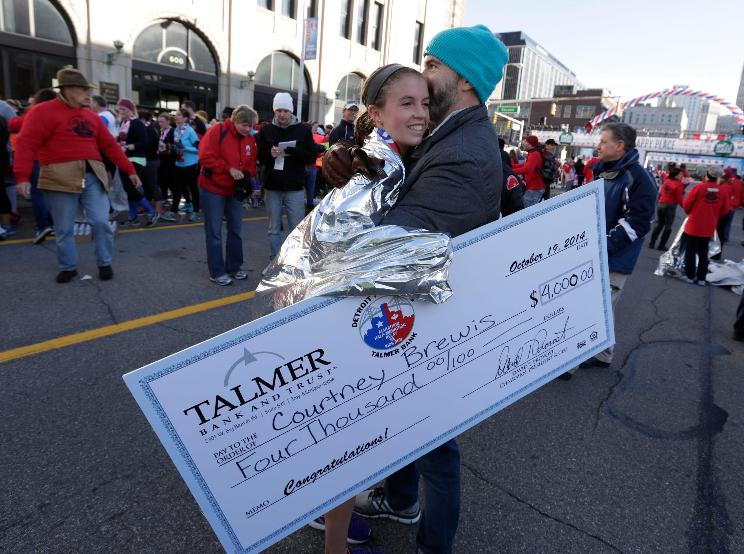 Courtney Brewis from Dearborn hugs her uncle Patrick Brewis after winning the women's division in the marathon during  the 37th Annual Detroit Free Press/Talmer Bank Marathon in Detroit on Sunday, Oct. 19, 2014.