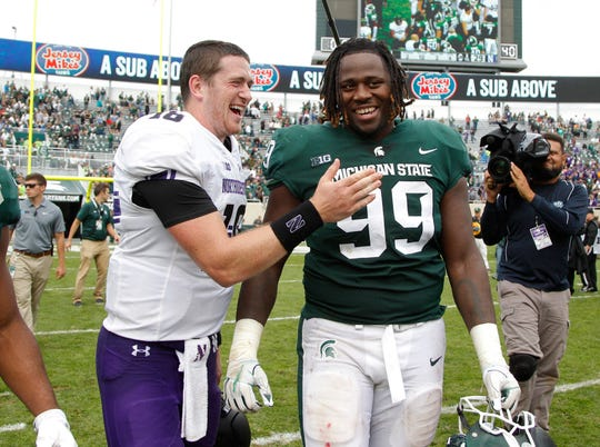 Northwestern quarterback Clayton Thorson, left, and Michigan State defensive tackle Raequan Williams talk following an NCAA college football game, Saturday, Oct. 6, 2018, in East Lansing.