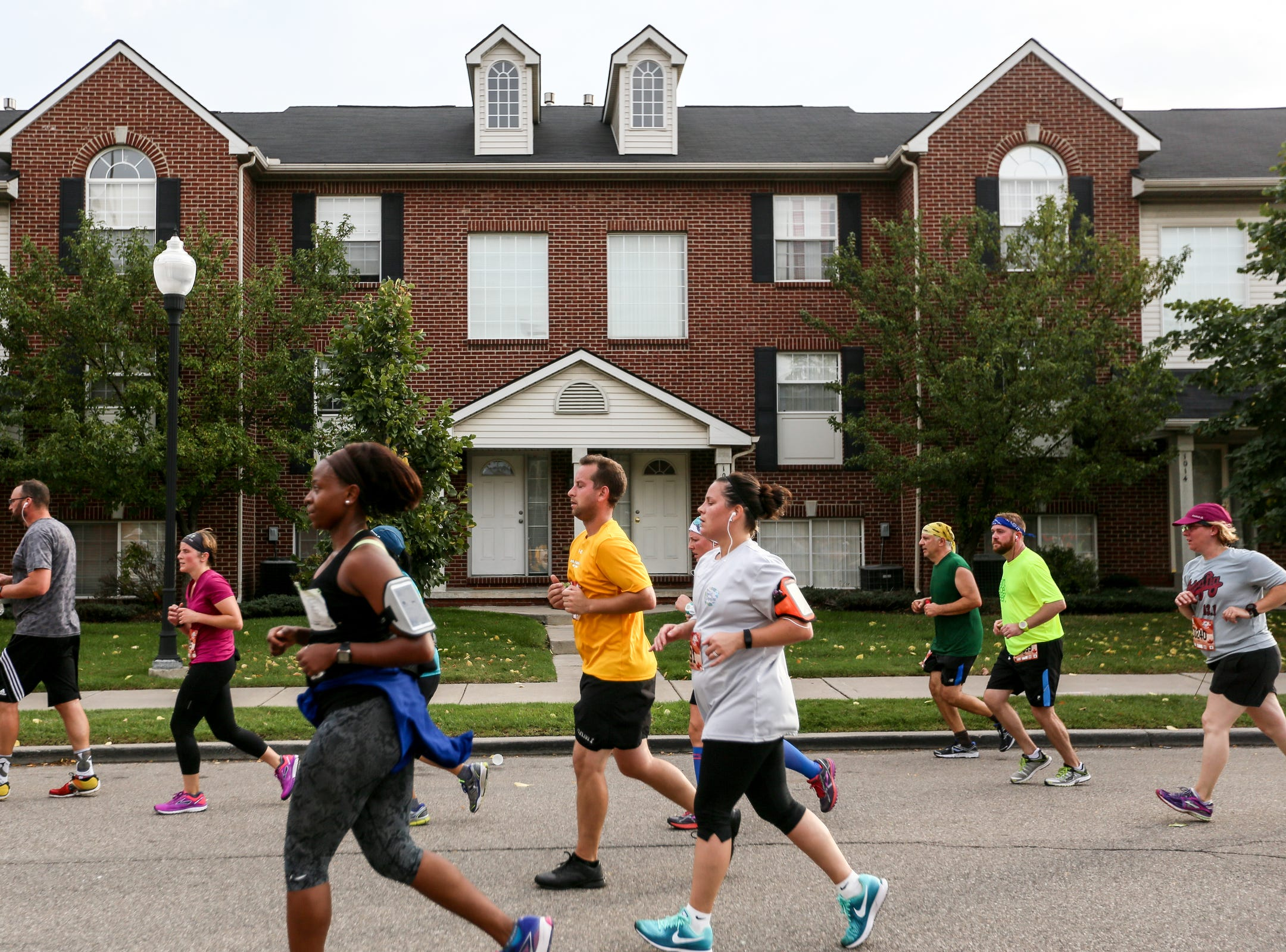 Runners pass by condos in Mexicantown during the 40th Annual Detroit Free Press/Chemical Bank Marathon in Detroit on Sunday, Oct. 15, 2017.