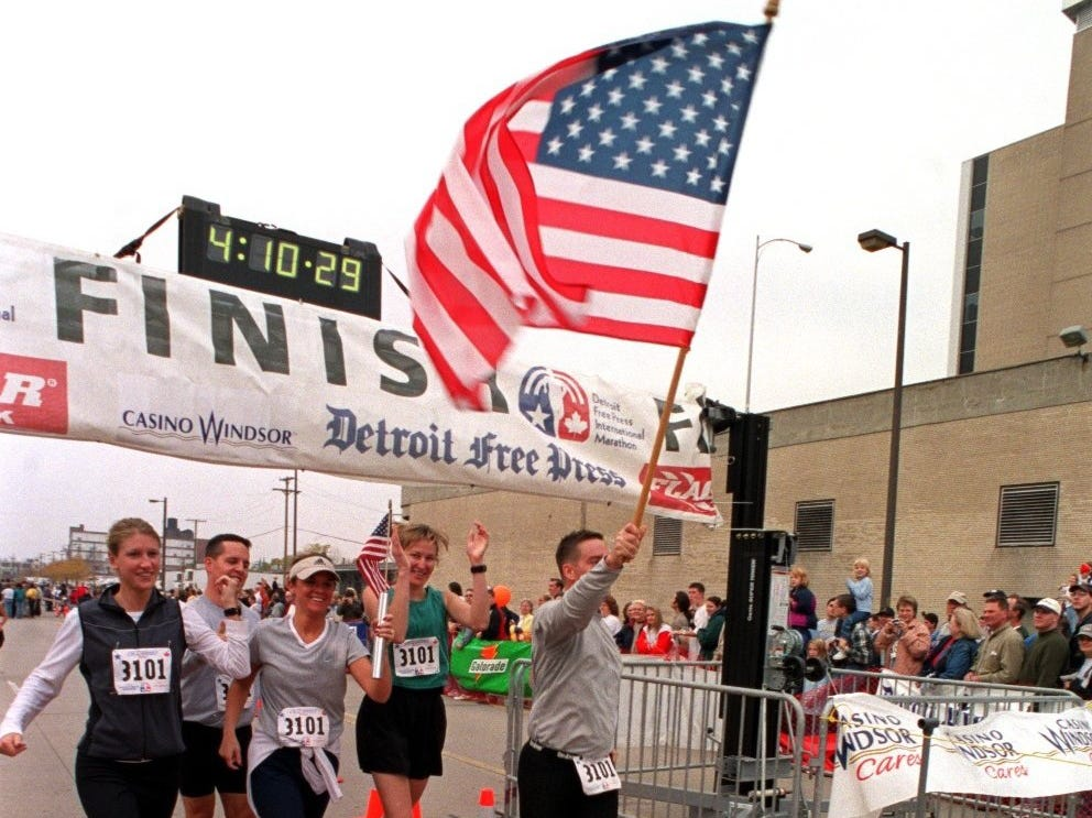A runner carrying an American flag and others cross the finish line of the Free Press/Flagstar International Marathon Sunday in Detroit in 2001.
