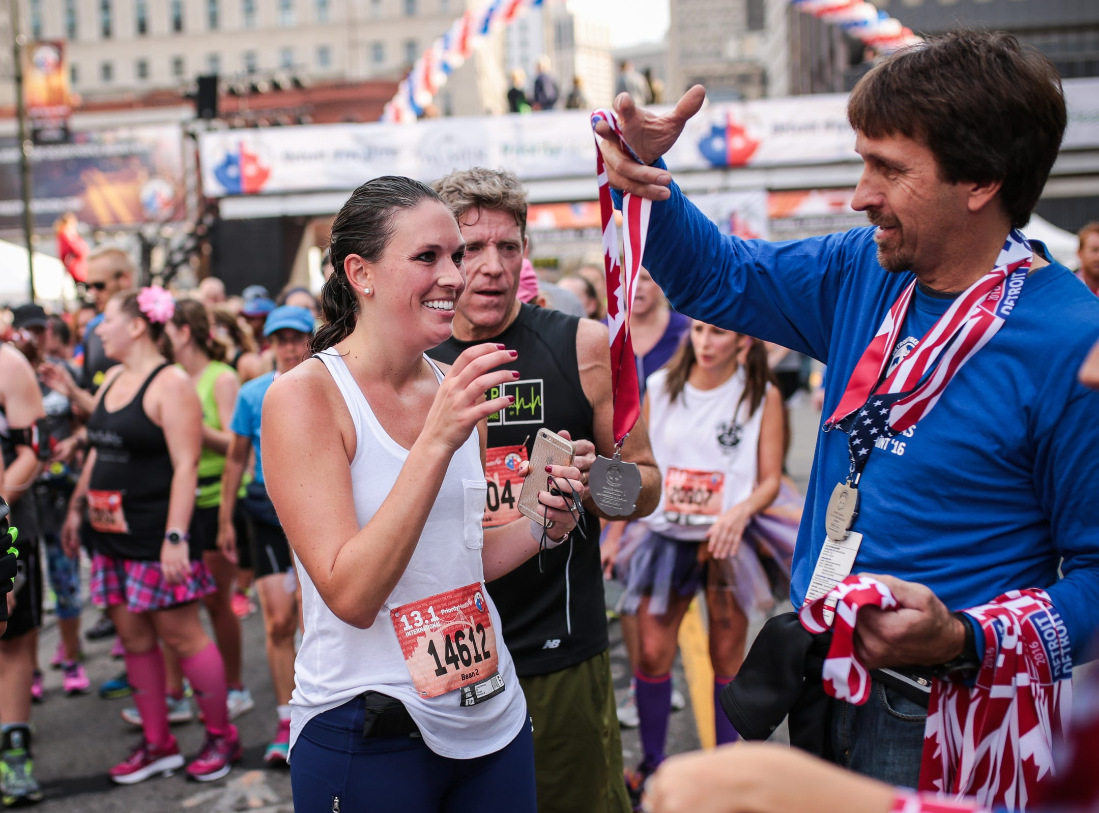 Emily Hyssong, of Ann Arbor, collects her medal after completing the International Half Marathon during the 39th Annual Detroit Free Press/Talmer Bank Marathon in Detroit on Sunday, Oct. 16, 2016.