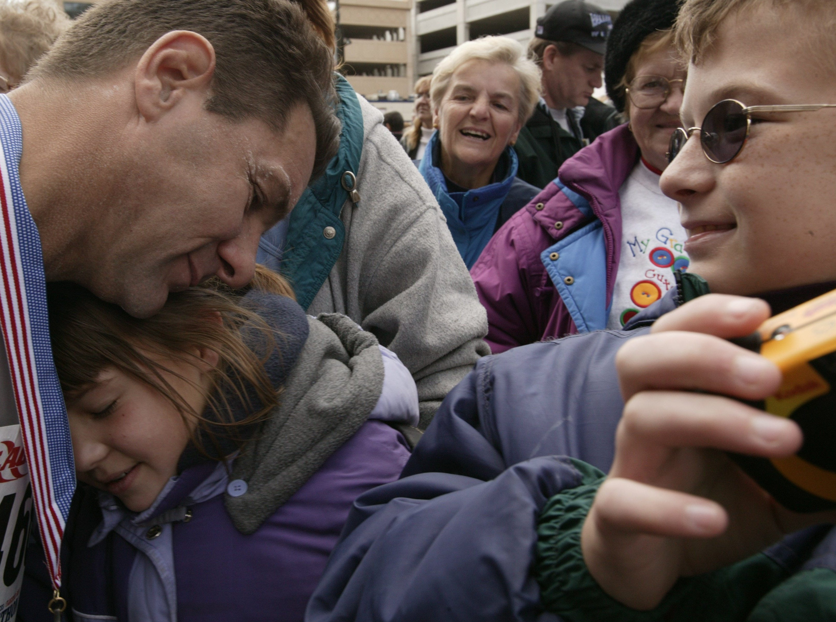 Marathon runner Lenny Olechiw of St. Clair Shores, 48, left, is congratulated for finishing his fourth marathon by his daughter Diana, 9, center, as his son Charles, 12, right, looks on outside of Ford Field in Detroit on Sunday, October 5, 2003.