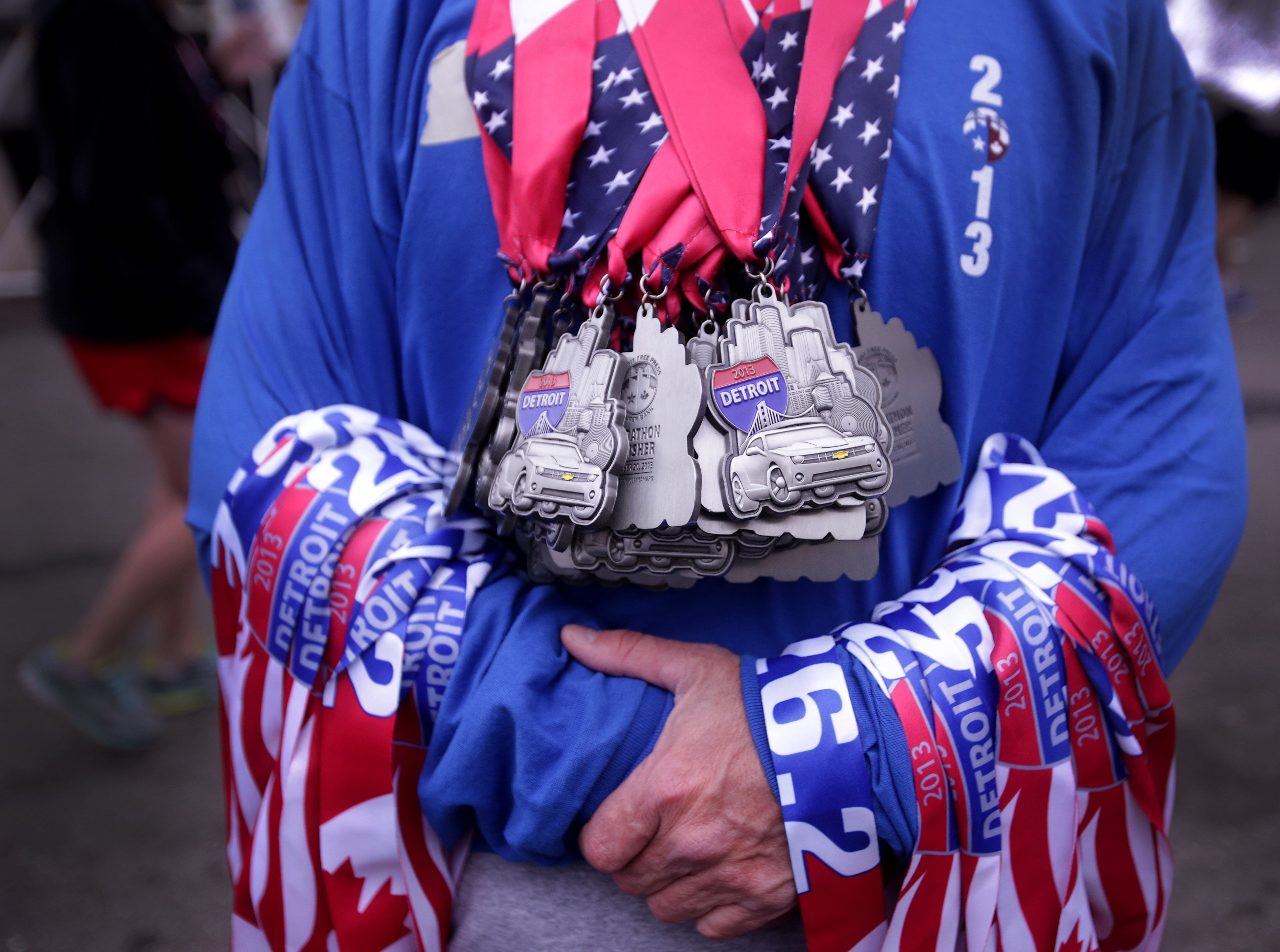 A volunteer holds the 26.2 marathon finisher medals at  the 36th Annual Detroit Free Press/Talmer Bank Marathon in Detroit Sunday, Oct. 20, 2013.