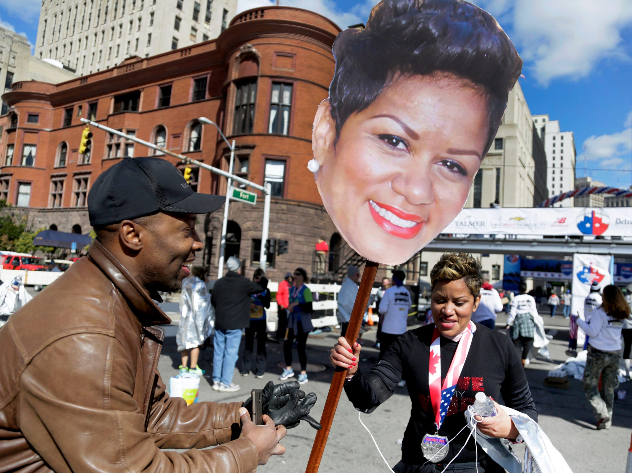 A proud Lance Maddox, 46, of Detroit, left, wanted to make sure his marathon running wife Tammy Turner-Maddox, 43, knew where to find him in the crowd so he made a big head cut-out of her for  the 38th Detroit Free Press/Talmer Bank Marathon Sunday Oct. 18, 2015.