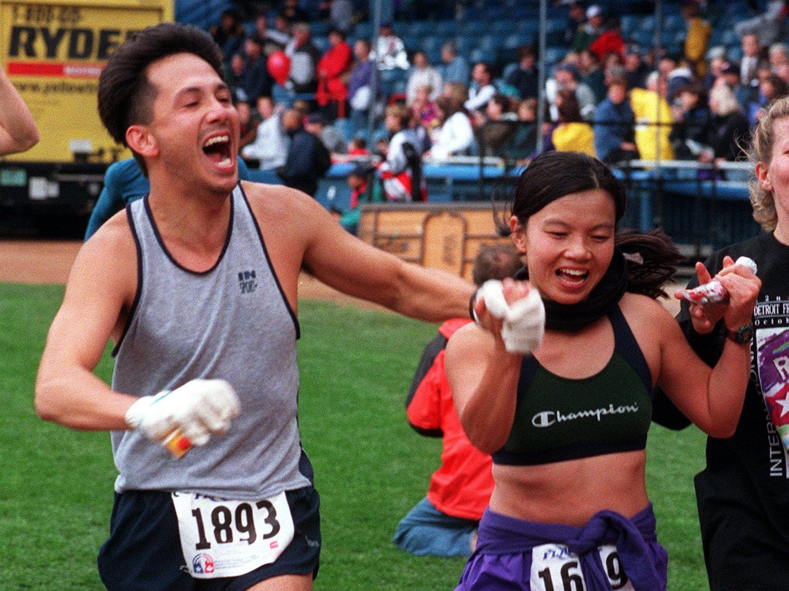 James Yee celebrates with Sarah Yee as they finish the Detroit Free Press/Flagstar Bank International Marathon Sunday, Oct. 17, 1999, at Tiger Stadium in Detroit.