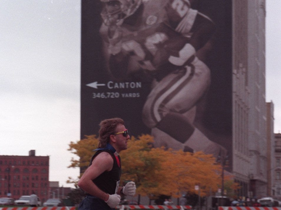 A marathon runner passes by the Barry Sanders mural on Woodward on his way toward Hart Plaza in Detroit in 1996.