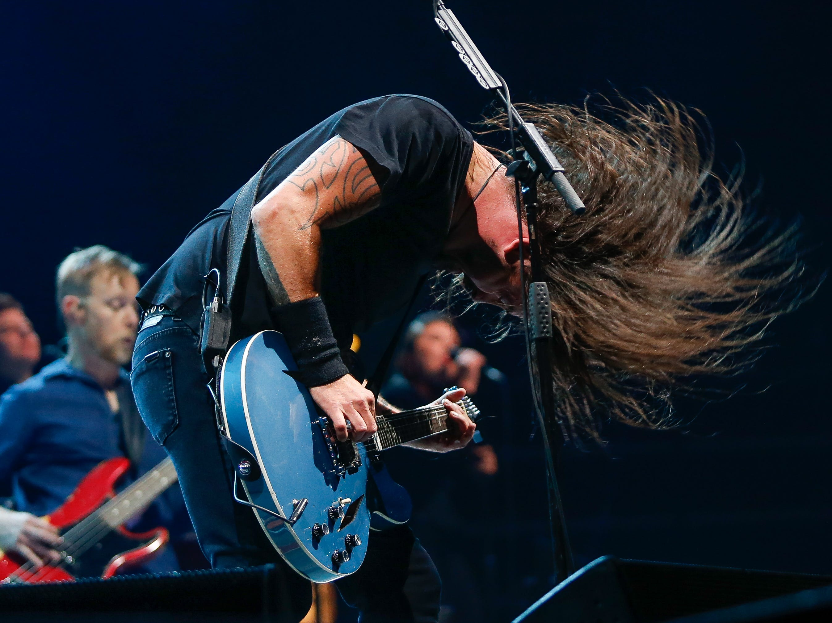 The Foo Fighters' Dave Grohl whips his long hair as he plays guitar Monday at Little Caesars Arena.