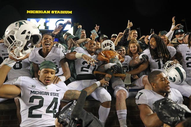Michigan State players celebrate with the Paul Bunyan Trophy after beating Michigan in Ann Arbor in 2017.