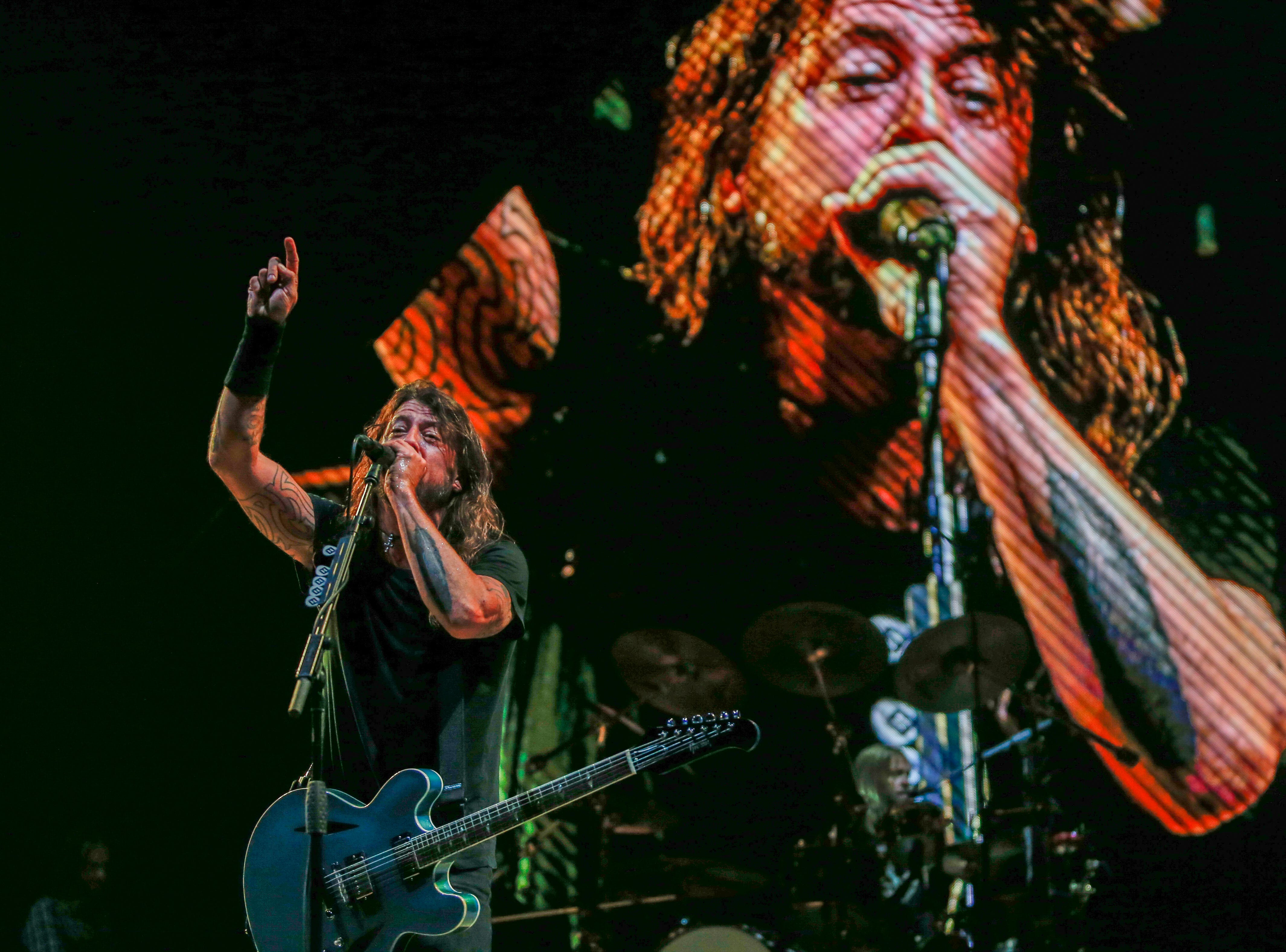 """Dave Grohl sings on stage as he's shown on the video board behind him during the Foo Fighters' """"Concrete and Gold"""" concert Monday at Little Caesars Arena."""