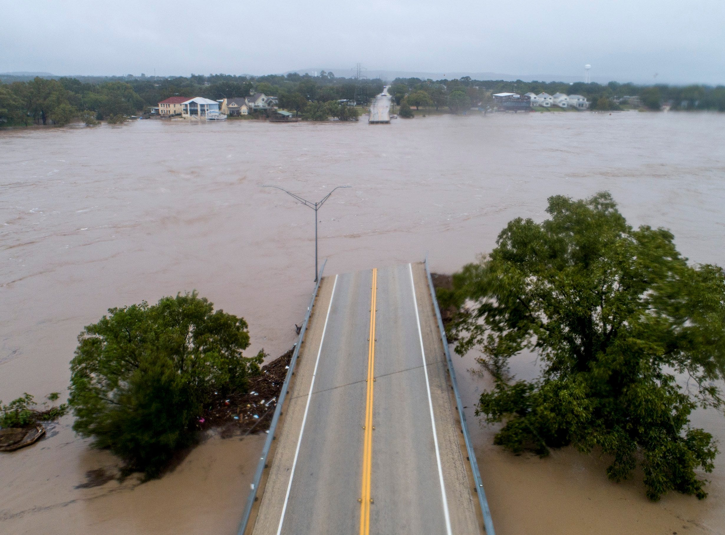 The Llano River flows between the washed out Ranch Road 2900 bridge, Tuesday, Oct. 16, 2018, in Kingsland, Texas.