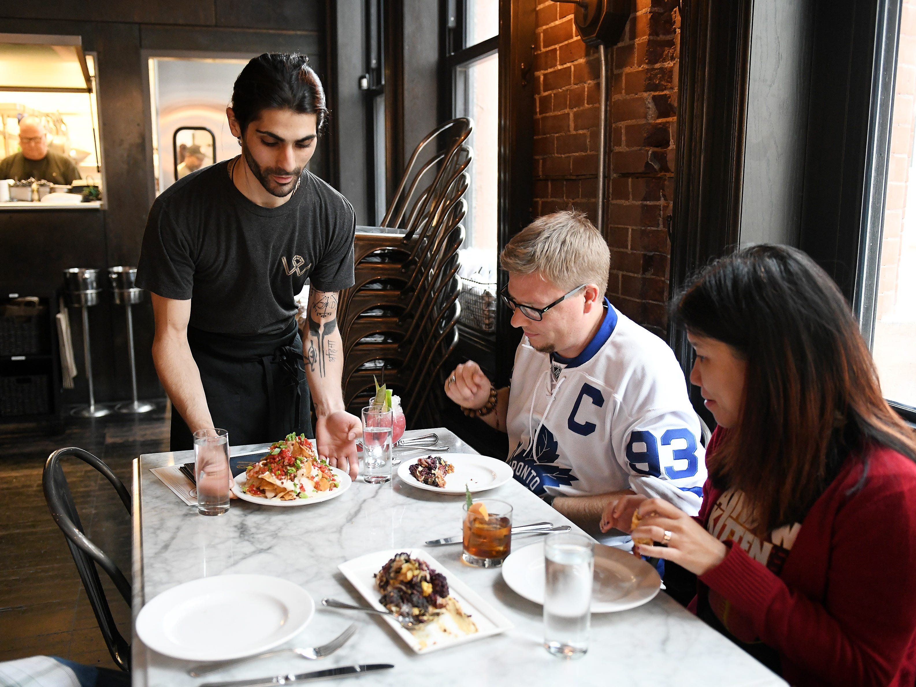 From left, Server Daniel Dehkordi serves fresh potato chips topped with white cheddar cheese, bacon, scallions, tomato and relish Russ Johnson of Calgary and Daisy Chang of East Lansing. (Robin Buckson / The Detroit News)