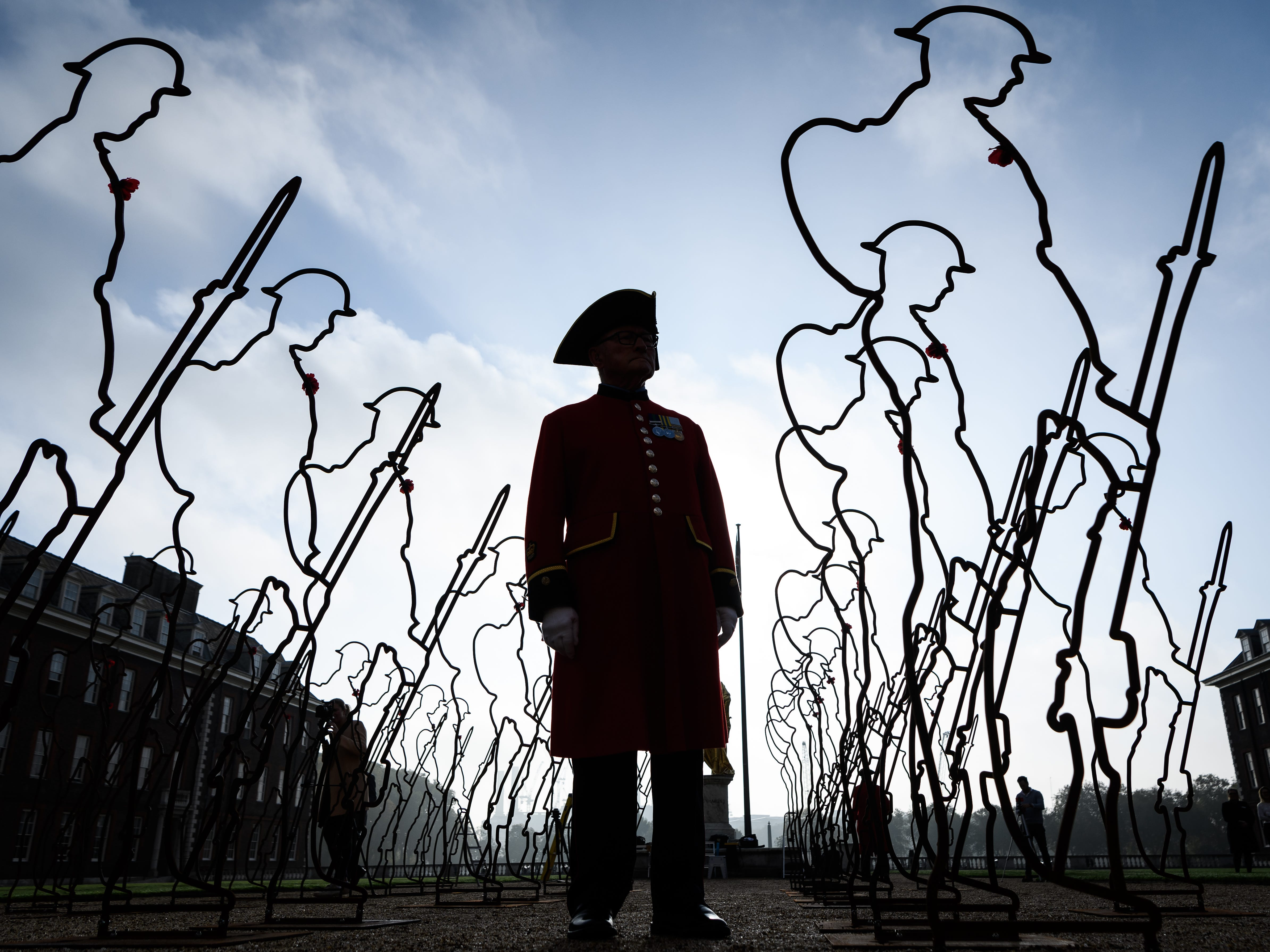"A former member of the armed forces, known as a Chelsea Pensioner, poses among the ""Tommy"" figures"" before taking part in a photograph to commemorate 100 years since the end of the First World War, at Royal Hospital Chelsea on Oct. 16, 2018, in London."