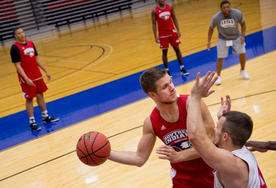 University of Southern Indiana's Alex Stein makes a baseline pass around defender Braden Fitzjerrells during the first practice of the season at the Physical Activities Center at USI Monday afternoon.