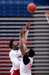 University of Southern Indiana's Hugues Mbumba shoots over teammate Emmanuel Little during the first practice of the season at the Physical Activities Center at USI Monday afternoon.