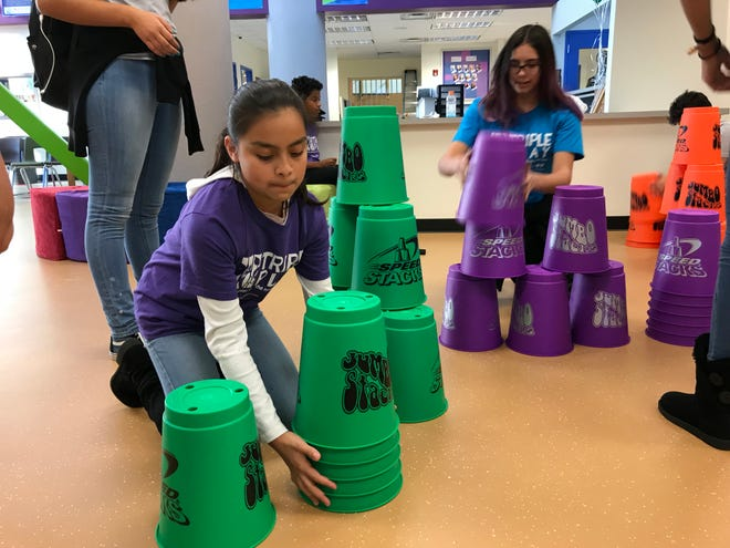 Ximena Herrera, 12, stacks giant cups as part of a Cupstacking relay at the Boys & Girls Club of Larimer County in this file photo.