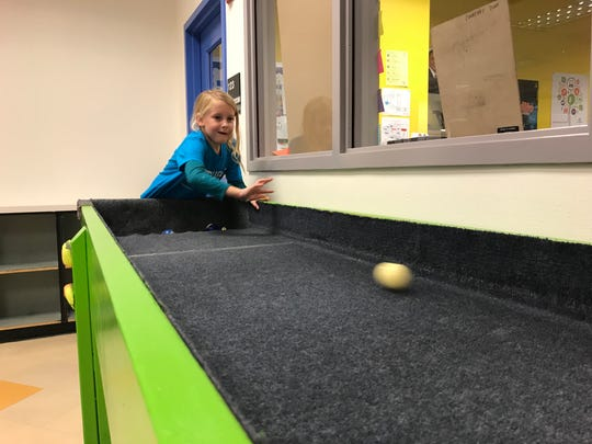 Mimi Patterson, 6, plays carpetball Monday at the Boys and Girls Clubs of Larimer County Fort Collins location. The club revealed upgrades to the games room Monday, made possible by a $20,000 grant.