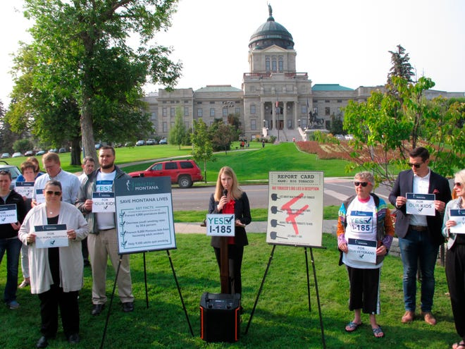 FILE--In this Aug. 22, 2018, file photo, Amanda Cahill of the American Heart Association speaks to a rally in support of a ballot initiative to raise Montana's tobacco taxes in Helena, Mont. Industry-funded opponents of Montana citizen's initiatives to raise the state's tobacco tax and add new mining regulations are vastly outspending the measures' supporters to put their messages in front of voters about a month before Election Day, according to campaign finance reports.(AP Photo/Matt Volz, file)
