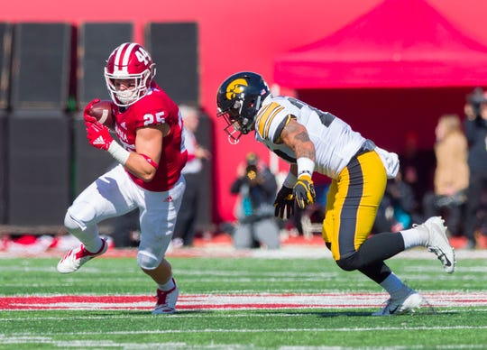 Indiana wide receiver Luke Timian (25) runs away from the defense of Iowa defensive back Amani Hooker (27) during the second half of an NCAA college football game Saturday, Oct. 13, 2018, in Bloomington.