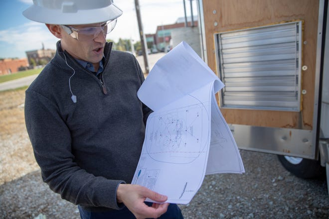 Andrew Horwath, director of engineering and remediation services at EnviroForensics, looks at a blueprint of a current remediation site, the Karstadt Reed site, near downtown Indianapolis on Tuesday, Oct. 16, 2018. The site was formerly the home of a dry cleaners.