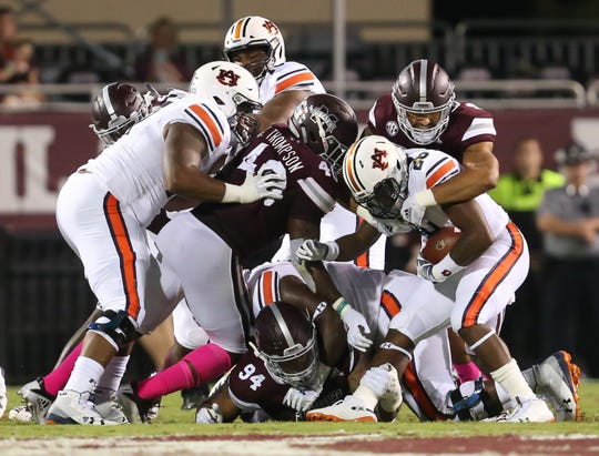 Mississippi State's Montez Sweat (9), Mississippi State's Erroll Thompson (40) and Mississippi State's Jeffery Simmons (94) plug the middle of the defensive line to stop Auburn's JaTarvious Whitlow (28). Mississippi State and Auburn played in an SEC college football game on Saturday, October 6, 2018, in Starkville. Photo by Keith Warren/Madatory Photo Credit