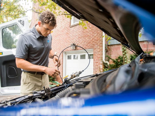 Pit Crew's Andrew Dacus siphons out the oil of a Toyota in its owner's driveway in Knoxville on Tuesday, October 16, 2018. Pit Crew is an on demand mobile auto service that can perform oil changes, tire rotations and wiper blade replacements wherever is most convenient to the customer.