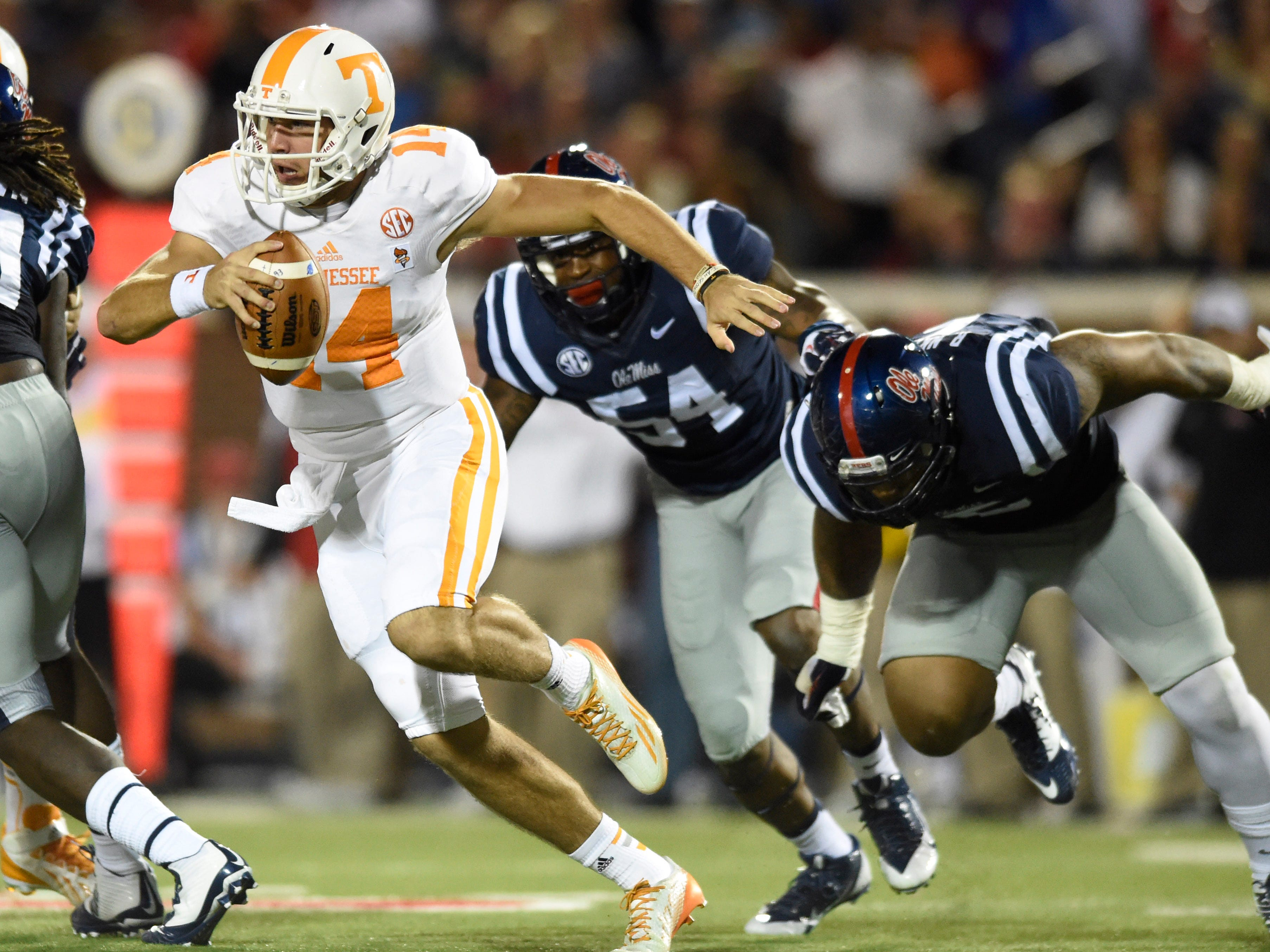 Tennessee quarterback Justin Worley (14) tries to escape the Ole Miss pass rush during the first half at Vaught-Hemingway Stadium, Saturday, Oct.18, 2014 in Oxford, Miss.