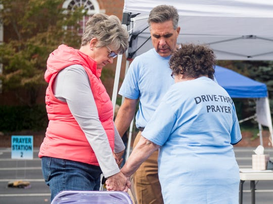 "Paul Pardue, head of prayer ministry at Central Baptist of Bearden, leads a prayer during the church's ""drive-thru prayer request"" event in Knoxville on Saturday, Oct. 13, 2018."