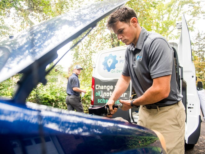 Pit Crew's Andrew Dacus adds oil to a Toyota in its owner's driveway in Knoxville on Tuesday, October 16, 2018. Pit Crew is an on demand mobile auto service that can perform oil changes, tire rotations and wiper blade replacements wherever is most convenient to the customer.