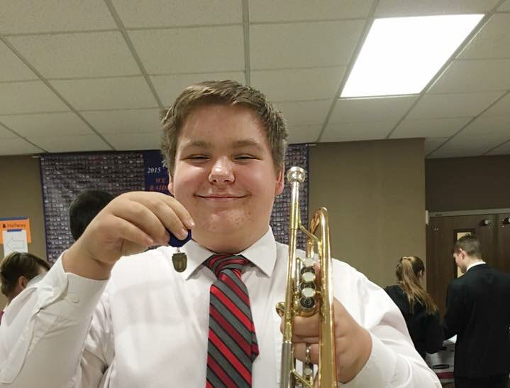 Holding his Gold medal after District Solo and Ensemble Competition for Trumpet.