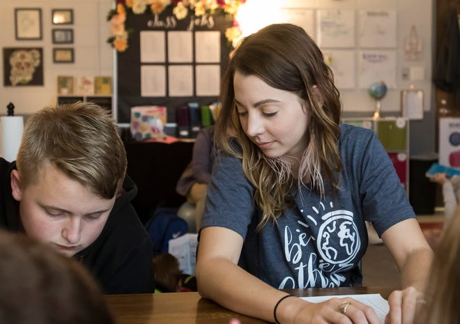 Amber Ball, 26, helps one of her students, Briar LaPrairie, at Caldwell Parish Junior High  in Columbia, La., on Sept. 18, 2018.