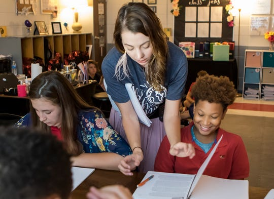 Amber Ball, 26, helps students Maddie Stephens and Cormaine Smith at Caldwell Parish Junior High  in Columbia, La., on Sept. 18, 2018.