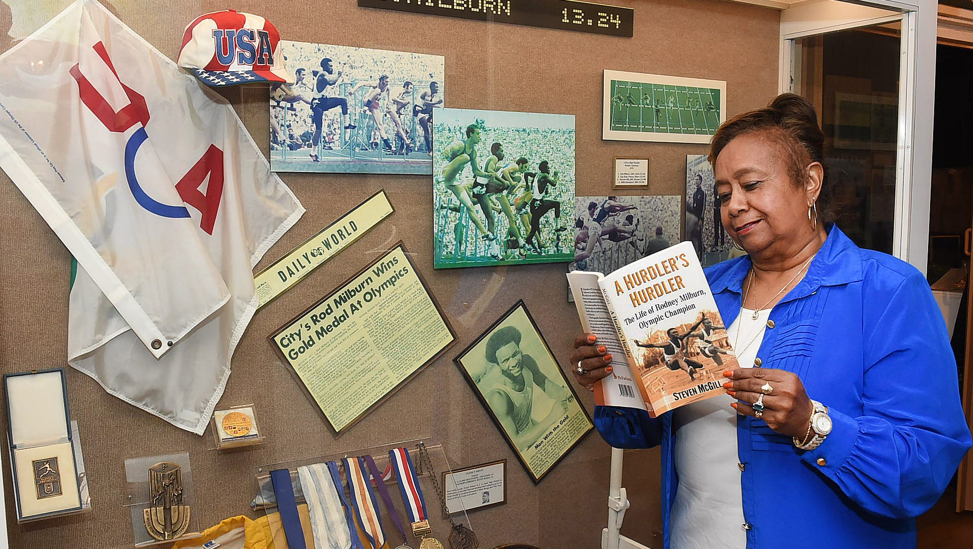 Lena Charles looks over a copy of the new biography of Olympic gold medalist Rodney Milburn at Milburn exhibit at the Opelousas Museum and Interpretive Center.
