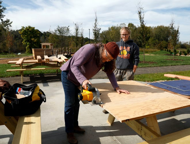 Amy Dutts, a playscape designer with Urban Wild Ltd., cuts a piece of plywood to make a chalk board as she and Miranda Fowler, a staff member of AHA! A Hands-On Adventure, A Children's Museum, create instillations for the children's museum's outdoor education and play area Tuesday, Oct. 16, 2018, in Lancaster.