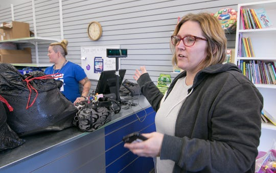 Beth Raymond brings in several bags of items Tuesday, Oct. 16, 2018 for possible sale to Once Upon a Child. Behind the counter is employee Stephanie Weigel.