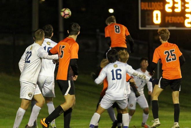 Brighton's Charlie Sharp (8) heads in the winning goal in a 1-0 victory over Walled Lake Central in the first round of district soccer play on Monday, Oct. 15, 2018.