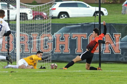 Brighton's Austin Lally tries to slide the ball past Walled Lake Central goalie Brian Ostapenko in a first-round Division 1 district soccer game on Monday, Oct. 15, 2018.