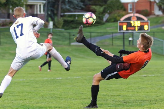 Brighton's Charlie Sharp (8) keeps the ball away from Walled Lake Central's Brandon Schweymaier (17) during a first-round district soccer game on Monday, Oct. 15, 2018.