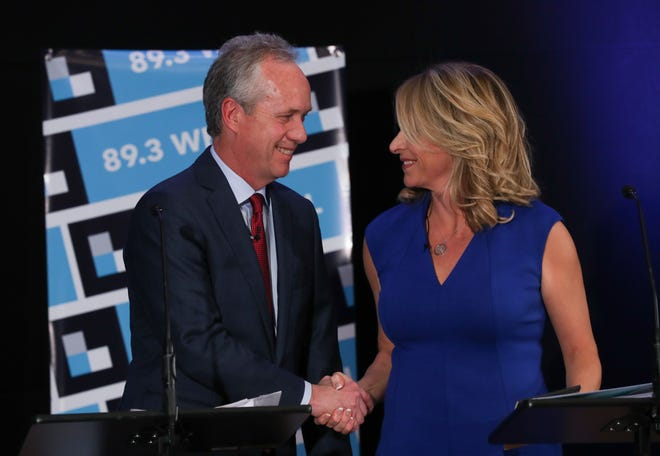 Mayor Greg Fischer, left and Councilwoman Angela Leet shook hands before their mayoral debate at the WFPL studio. Oct. 16, 2018