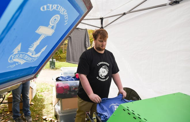 Nathan Dunsmore of St. Johns, 27, pulls a freshly minted T-shirt design he created from the dryer Friday, Oct. 12, 2018, during the 2018 Color Cruise and Island Festival in downtown Grand Ledge. His design for a St. Johns print shop allows wearers to display how much in student debt they conquered.
