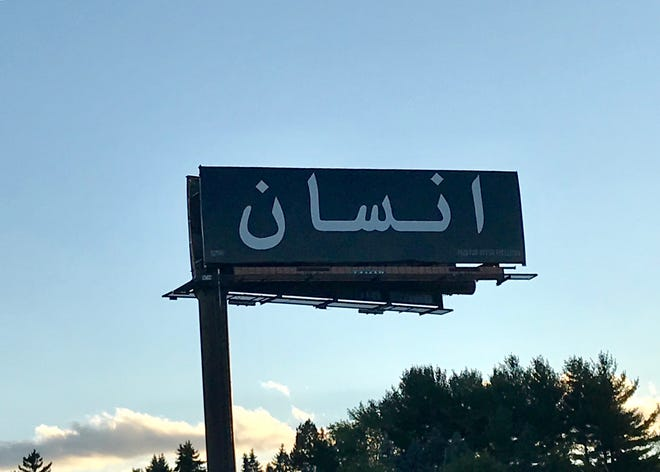 """Jamila El Sahili's artwork on a billboard facing southbound traffic on I-69 in Windsor Township reads """"human being"""" in Arabic."""