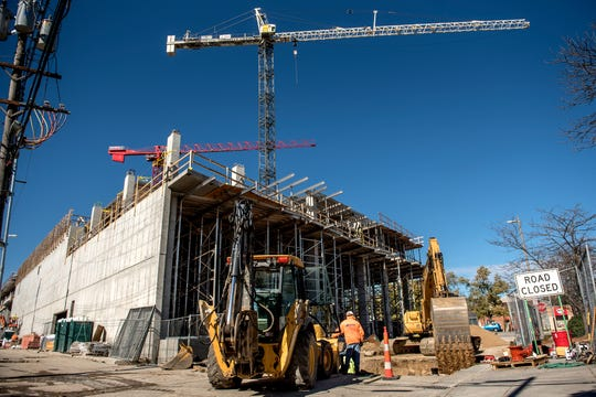 Construction crews work on The Hub on Tuesday, Oct. 16, 2018, in East Lansing. It's one of three mixed-use developments planned or under construction in East Lansing's downtown.