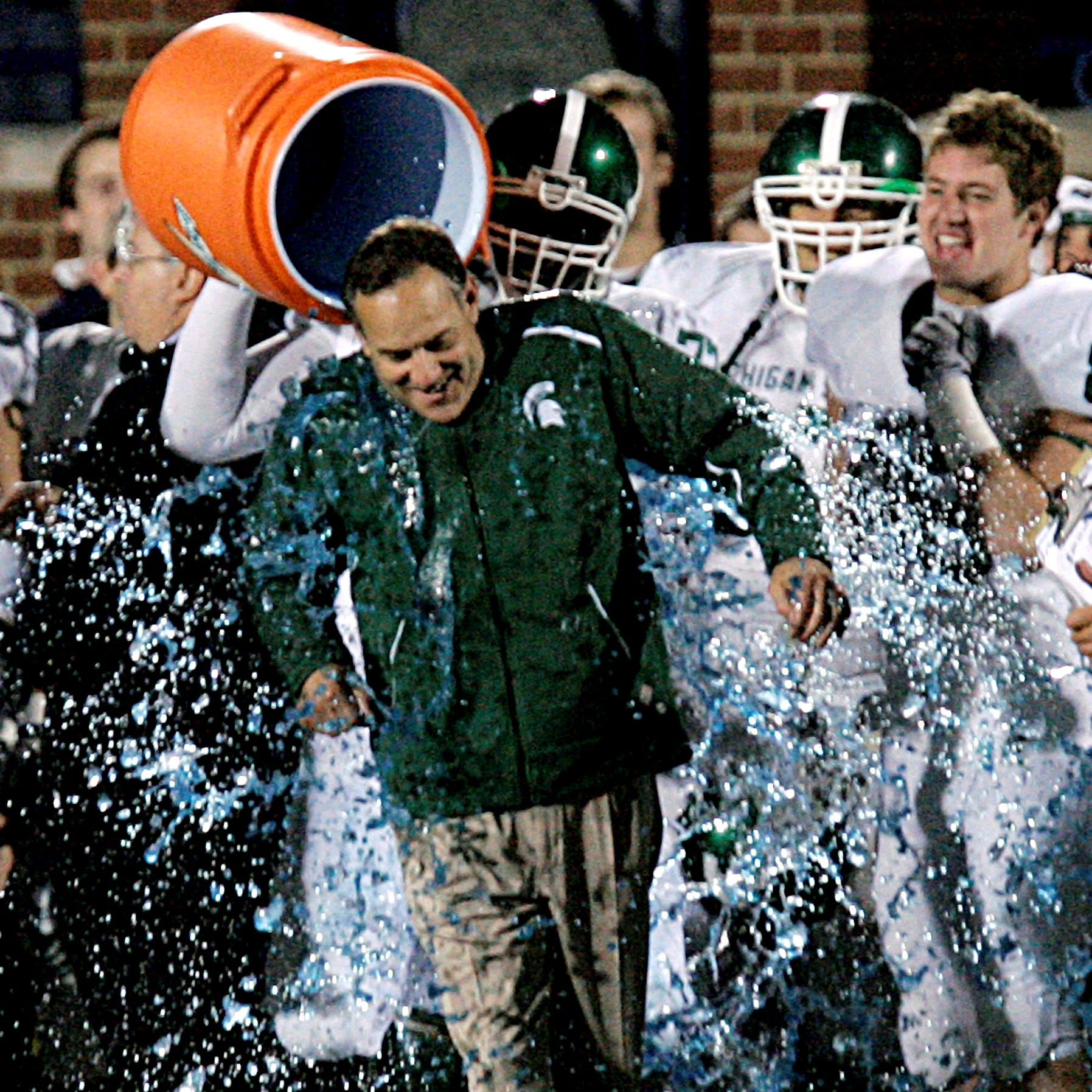 A Michigan State player pours a sports drink on head football coach Mark Dantonio during the closing seconds of their 35-21 win over Michigan in an NCAA college football game in Ann Arbor, Mich., Saturday, Oct. 25, 2008. (AP Photo/Carlos Osorio)
